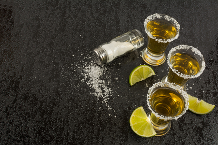 tequila: Gold tequila with lime on black background, top view. Tequila shot. Tequila. Gold Mexican tequila