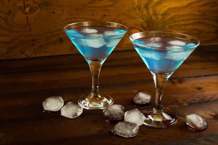 blue hawaiian drink: Two glasses of blue cocktail on dark wooden background. Blue Martini. Blue Hawaiian cocktail. Stock Photo