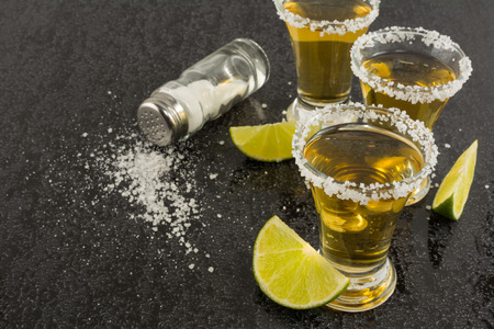 fruit of the spirit: Shots of gold tequila with lime and salt on the black background. Tequila shot. Gold Mexican tequila. Tequila. Stock Photo