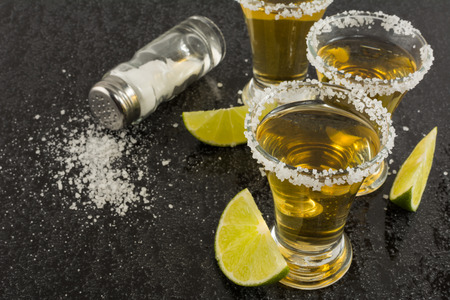 tequila: Gold tequila shots with lime on black background. Gold Mexican tequila. Tequila shot. Tequila.