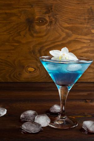 blue hawaiian drink: Blue cosmopolitan cocktail on wooden background. Blue margarita. Blue cosmopolitan. Blue Lagoon. Blue cocktail. Blue Martini. Blue Hawaiian cocktail. Blue curacao liqueur.