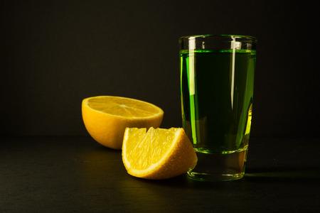 ajenjo: Absenta y cal sobre fondo negro. bebida de alcohol. Bebida verde de alcohol
