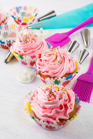 gourmet kitchen: Pink cupcakes  and kitchen utensils, vertical. Birthday cupcakes. Homemade cupcake. Sweet dessert. Gourmet cupcakes. Sweet cupcake. Sweet pastry.