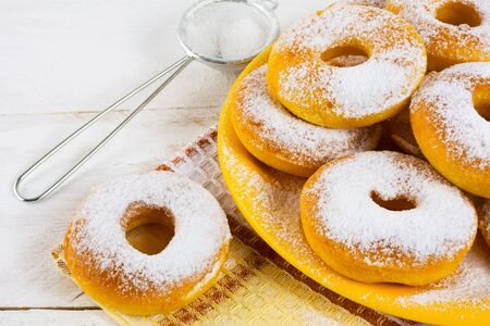 caster: Homemade donuts powdered by caster sugar. Doughnuts. Sweet pastry. Donuts. Sweet dessert.