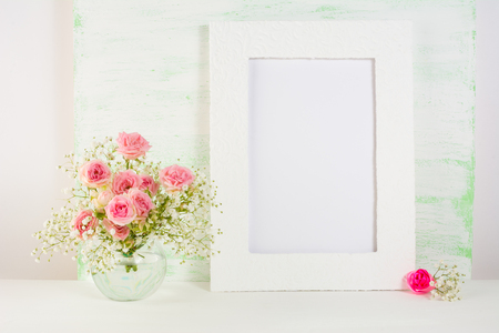 Frame mockup with roses in vase. Frame mockup. Poster Mockup. Styled mockup. Product mockup.  Design Mockup. Empty frame mockup. White frame mockup. Portrait frame mockup. Stock Photo