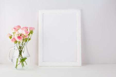 Frame mockup with pink roses. Frame mockup. White frame mockup. Poster Mockup. Styled mockup. Product mockup.  Design Mockup. Empty frame mockup. Portrait frame mockup. Stock Photo