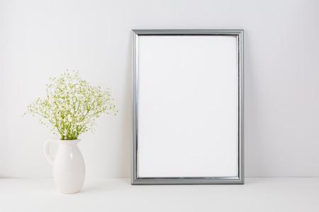 Frame mockup with white tender flowers. Frame mockup. Poster Mockup. Styled mockup. Product mockup.  White frame mockup. Design Mockup. Silver  frame mockup. 版權商用圖片