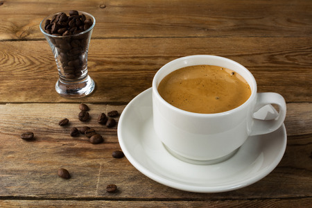 cup: Coffee cup and coffee beans on rustic background. Cup of coffee. Strong coffee. Morning coffee. Coffee break. Coffee mug.  Coffee cup.