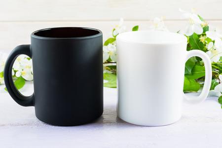 black white: White and black mug mockup with apple blossom. Coffee cup mockup. Empty mug mockup for product presentation.