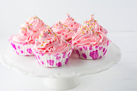 dessert stand: Decorated pink birthday cupcakes  on the cake stand. Sweet dessert  pastry with whipped cream. Birthday homemade cupcakes served for party.