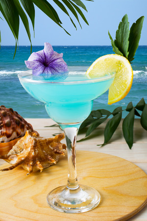 blue hawaiian drink: Blue Hawaiian cocktail on the tropical beach. Iced blue cosmopolitan cocktail. Blue Lagoon margarita martini cocktail. Summer beach alcohol drink Stock Photo
