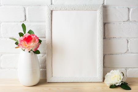 Model met wit montuur met roze en witte rozen. Mock-up van het portret of de poster met het witte kader. Leeg wit frame mockup voor ontwerppresentatie.