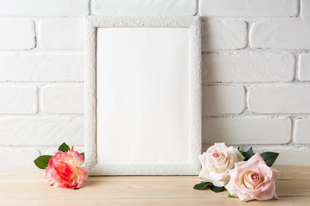 White frame mockup with roses. Empty white frame mockup for design presentation. Portrait or poster white frame romantic style mockup 版權商用圖片