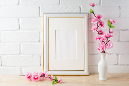White frame mockup with pink flower bunch. Empty white frame mockup for design presentation. Portrait or poster white frame mockup romantic style. Stock Photo