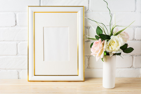 White frame mockup with pale pink roses in vase. Portrait or poster white frame mockup. Empty white frame mockup for presentation artwork.