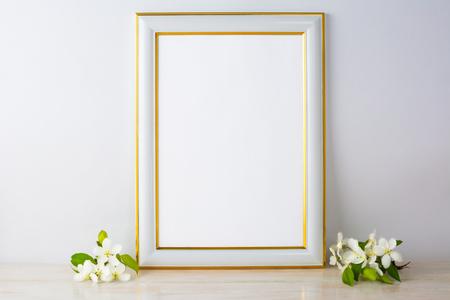 White frame mockup with apple blossom. Empty white frame mockup for design presentation. Portrait or poster white frame mockup romantic style.