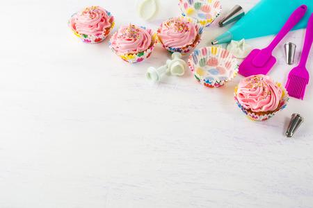 utensilios de cocina: pastelitos de color rosa y fondo de la invitación utensilios de cocina. magdalenas del cumpleaños. Fondo de cumpleaños. magdalena casera. maqueta de cumpleaños. Foto de archivo
