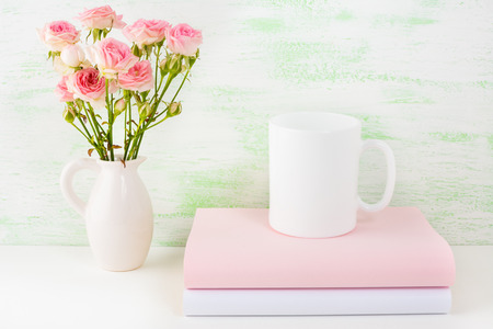 Coffee mug mockup with books and pink roses. Coffee cup mock-up for brand promotion.  Empty mug mockup for design presentation. Stock Photo