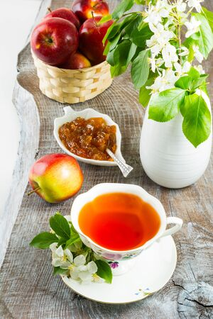 white backing: Cup of tea and apple jam on rustic wooden table. Homemade apple marmalade for tea time. Breakfast tea with sweet apple confiture. Stock Photo