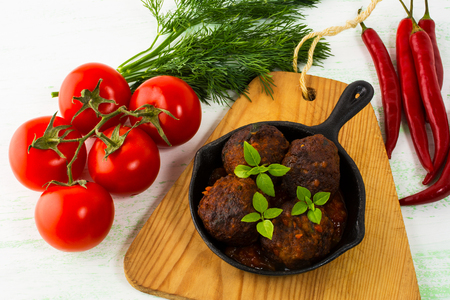 Grilled meatballs with chili pepper and tomato served in cast iron skillet.  Grilled bbq meatloaf. Barbecue Meatballs.