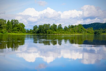 Beautiful landscape with blue sky and white clouds reflected in the clear river water. Wooded waterside of a mountain lake. Summer idyllic landscape.