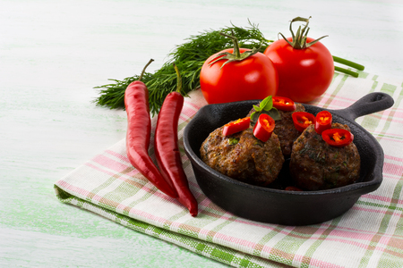 albondigas: Grilled meatballs served with chili pepper slices in cast iron skillet.  Grilled bbq meatloaf. Barbecue Meatballs.