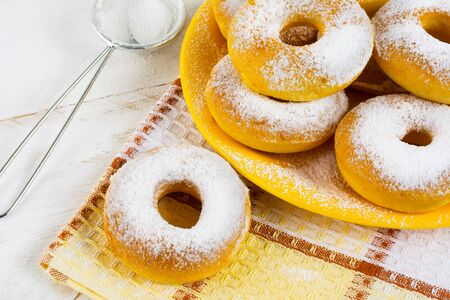 caster: Homemade sweet donuts with caster sugar on checkered napkin. Hanukkah sweet donuts. Sweet dessert pastry doughnuts.