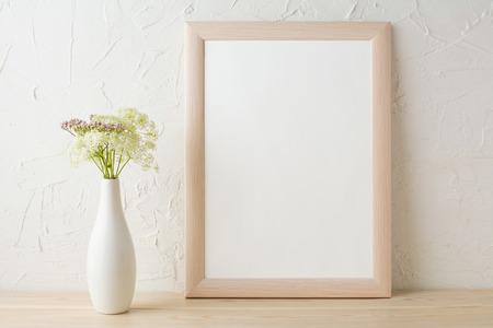 Frame mockup with tender flowers in white stylish vase. Poster white frame mockup. Empty white frame mockup for presentation design.