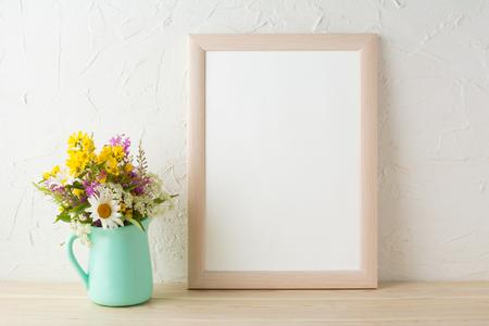 Frame mockup with tender flowers in mint green vase. Poster white frame mockup. Empty white frame mockup for presentation design.