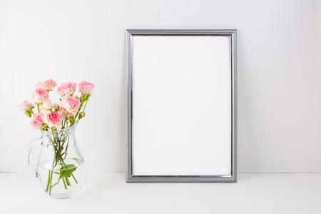 Silver frame mockup with pink roses. Portrait or poster white frame mockup. Empty white frame mockup for presentation artwork.