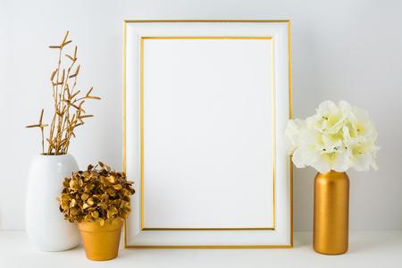 Frame mockup with ivory hydrangea in the  golden vase, white vase and golden flower pot. Poster white frame mockup. Empty white frame mockup for presentation artwork. 版權商用圖片