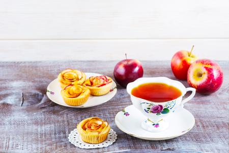 white backing: Cup of tea and apple roses shaped muffins on rustic wooden table. Sweet apple dessert pie. Homemade apple rose pastry. Breakfast tea with sweet apple pastry Stock Photo