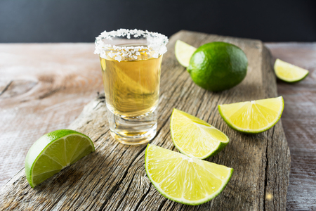 Tequila shot with lime on rustic wooden background. Strong alcohol  drink. Gold Mexican tequila shot.