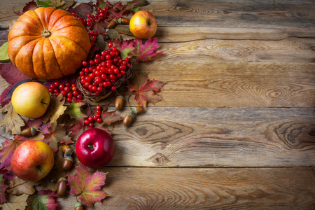 Thanksgiving  greeting background with pumpkins, apples and fall leaves. Thanksgiving background with seasonal vegetables and fruits. Stock Photo