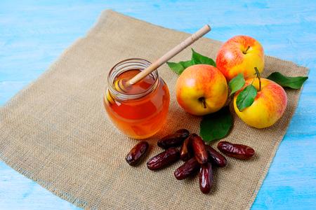 Honey jar, dates and apples on blue wooden background. Rosh hashanah concept. Jewesh new year symbols. 版權商用圖片