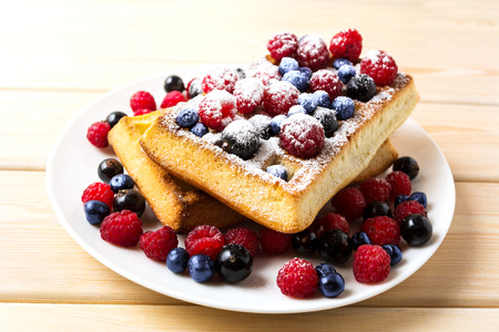 batters: Soft waffles with blueberry and raspberry. Breakfast soft waffles with fresh berries. Belgian waffles. Stock Photo