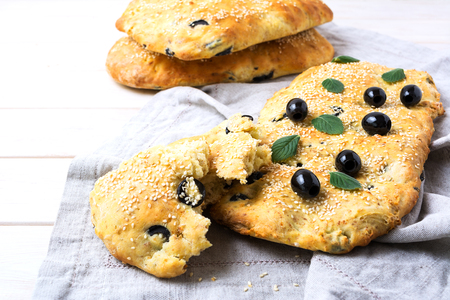 Focaccia with olive, garlic and herbs. Homemade traditional Italian bread focaccia on the linen napkin.