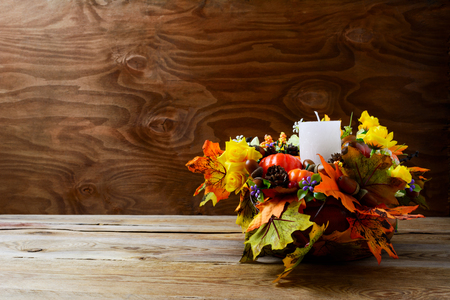 centerpiece: Thanksgiving decoration with silk fall leaves on rustic background. Thanksgiving greeting with fall decor. Fall centerpiece. Thanksgiving background. Copy space. Stock Photo