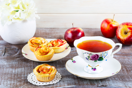 Cup of tea and muffins with rose shaped apple slices. Sweet apple dessert pie. Homemade apple rose pastry. Breakfast tea with sweet apple pastry Stock Photo