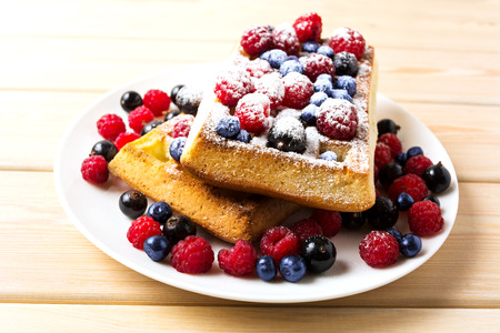 caster: Belgian waffles with blueberry and raspberry powdered by caster sugar. Breakfast soft waffles with fresh berries.