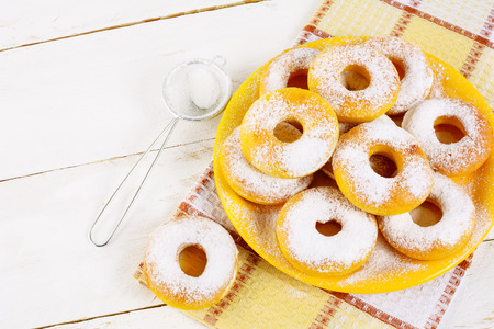 caster: Donuts with caster sugar served on yellow plate top view copy space. Sweet dessert pastry doughnuts.   Hanukkah sweet donuts.