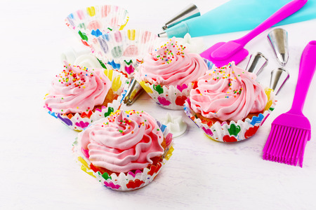 Cupcakes with pink whipped cream swirl and confectionery syringe. Birthday cupcake with pink whipped cream. Homemade decorated cupcakes. Stock Photo