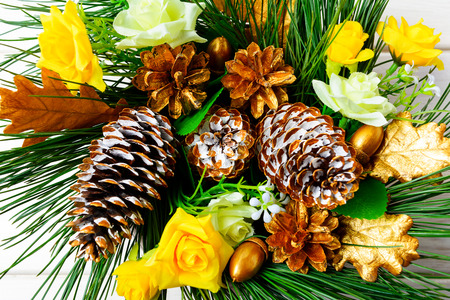 Christmas background with golden decorated pine cones and silk roses. Christmas party decoration, top view.