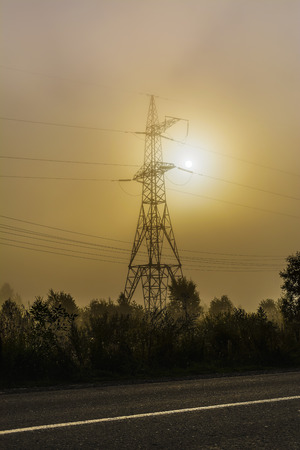 High voltage transmission tower near rural road. Electrical energy wire on morning mist background. Stock Photo