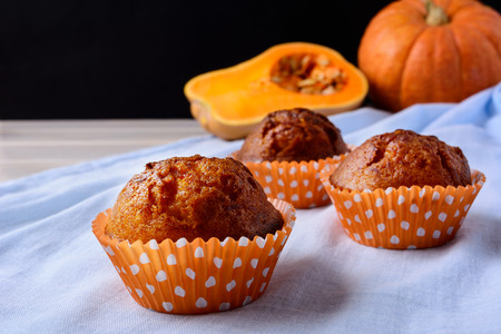 wrappers: Pumpkin muffins in the orange wrappers on the blue napkin. Fall seasonal homemade vegetable food.