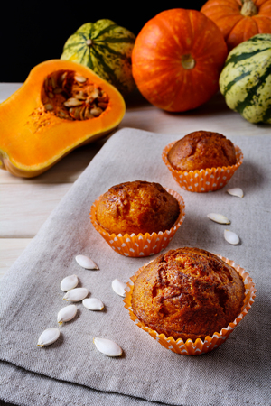 wrappers: Pumpkin muffins in the orange wrappers with squash seeds. Fall seasonal homemade vegetable food. Healthy vegetarian pastry.