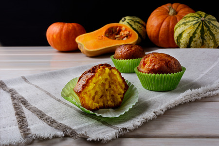 wrappers: Spiced butternut squash muffins in the green wrappers. Fall seasonal vegetable food. Thanksgiving homemade sweet pastry.