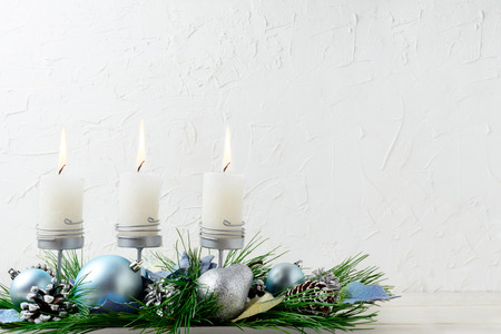 centerpiece: Christmas background with blue ornaments and burning candles. Christmas table centerpiece decoration. Copy space.