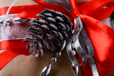 Christmas gift decoration with red ribbon and silver cone. Christmas greeting background.