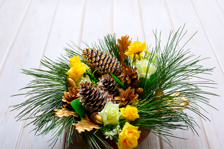 centerpiece: Christmas table centerpiece with golden pine cones and fir branches. Christmas background with golden decor. Stock Photo